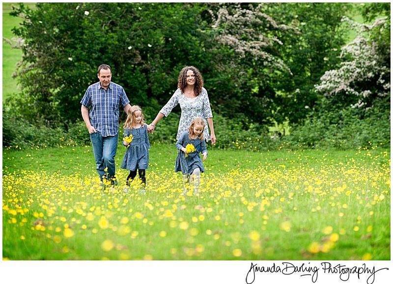 Family walking through a field of buttercups ny Surrey family photographer Amanda Darling